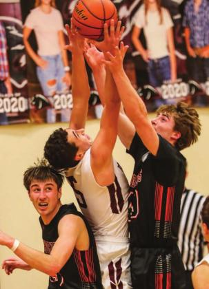 Timber Lake senior Trenton Hansen fights for a rebound between Faith's Tyson Selby (L) and Joel Gifford.